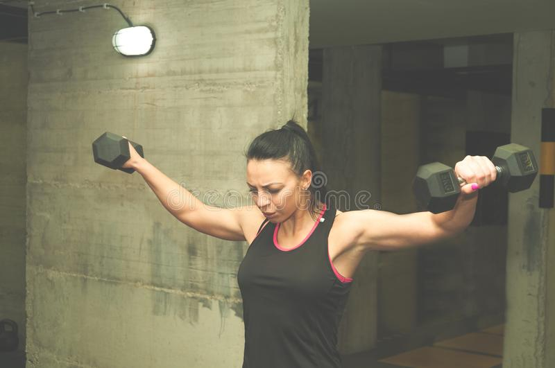 Beautiful young attractive girl dumbbell weights workout for shoulder muscles, real people training no posing, strength and condit. Ion concept royalty free stock photography