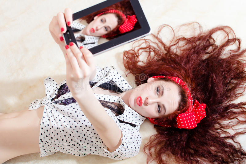 Beautiful young attractive woman pinup girl lying and taking selfy or selfie picture on digital tablet computer royalty free stock image
