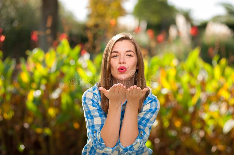 Attractive woman sends an air kiss to the camera royalty free stock image