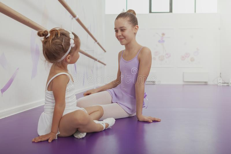 Charming two young ballerinas practicing at ballet class royalty free stock images