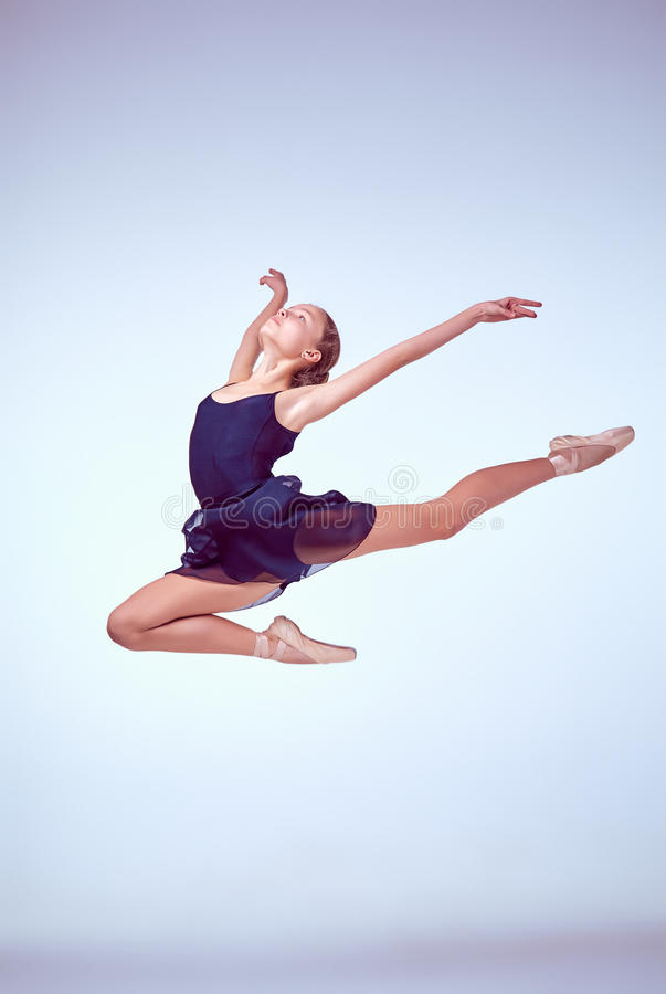 Beautiful young ballet dancer jumping on a gray stock photo