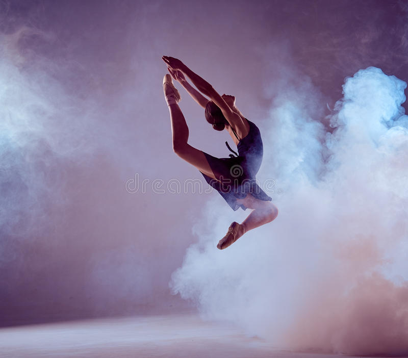 Beautiful young ballet dancer jumping on a lilac royalty free stock photos