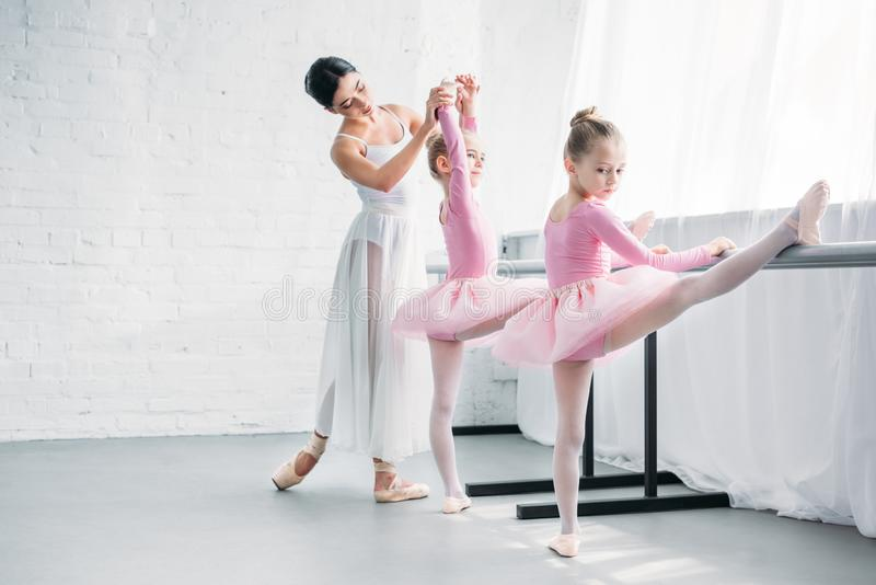Beautiful young ballet teacher exercising with kids. In ballet school royalty free stock images