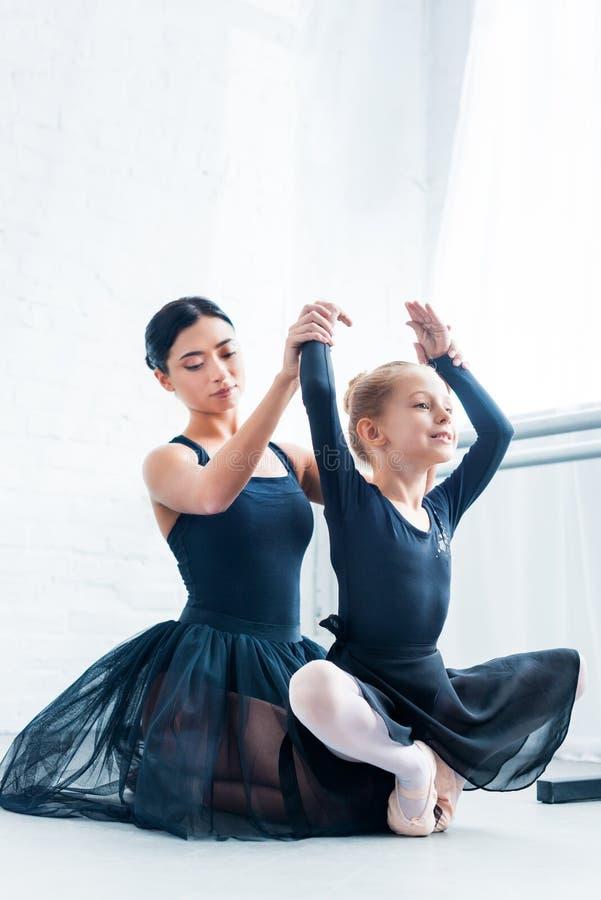 beautiful young ballet teacher training adorable flexible kid in ballet stock photo