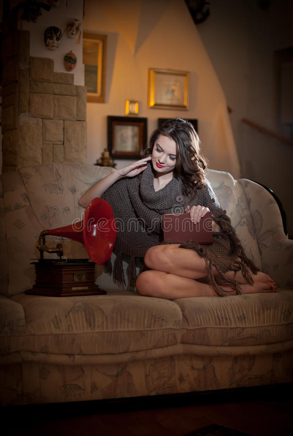 Beautiful young bare feet woman sitting on sofa holding a book having a red gramophone near her, vintage scenery royalty free stock images