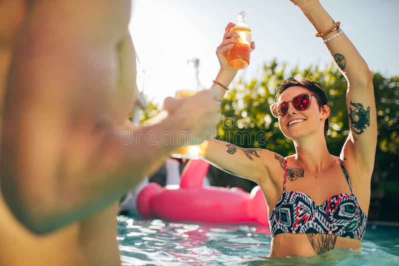 Woman partying with friends in swimming pool stock photos