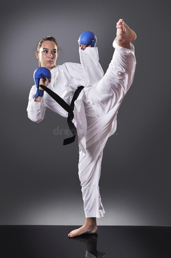 Beautiful young black belt female karate doing kick royalty free stock photo