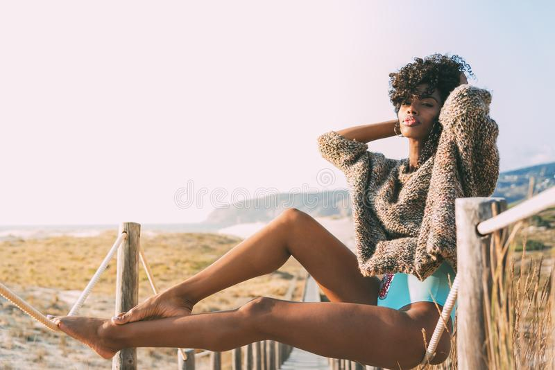 Beautiful young black woman sitting in a wooden foot bridge at. The beach stock photography