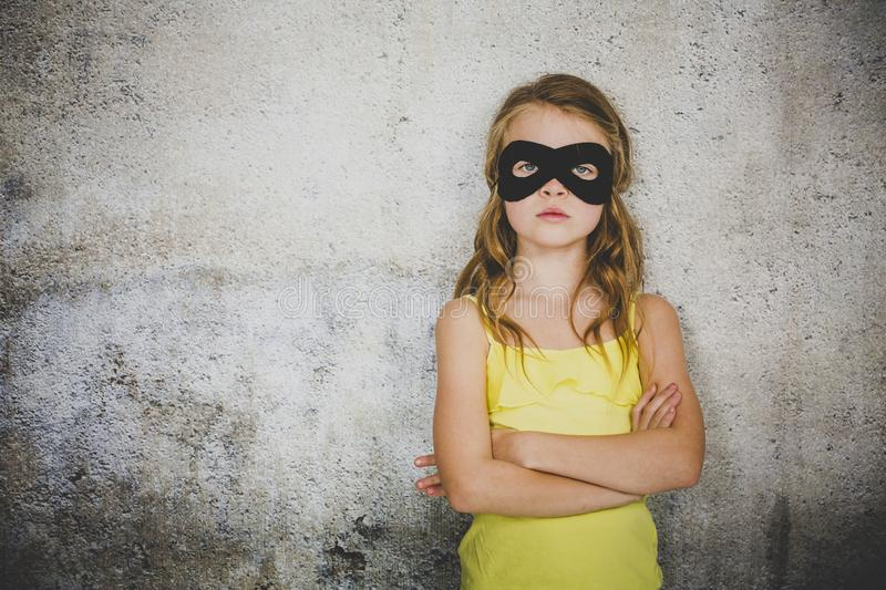 Blond girl with black superhero mask and yellow shirt is posing in front of concrete background. Beautiful and young blond girl with black superhero mask and stock photography