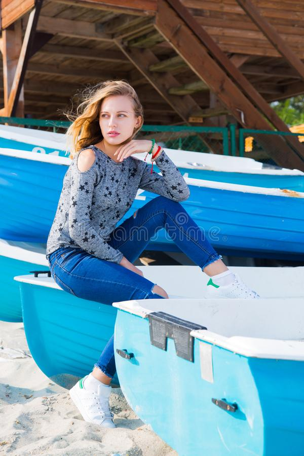 Beautiful young blond girl in jeans and sneakers sitting on blue boat on beach. royalty free stock photo