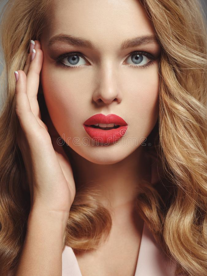 Beautiful young blond girl with red lips. Photo of a beautiful young blond girl with red lips. Closeup attractive sensual face of white woman with long curly stock photography
