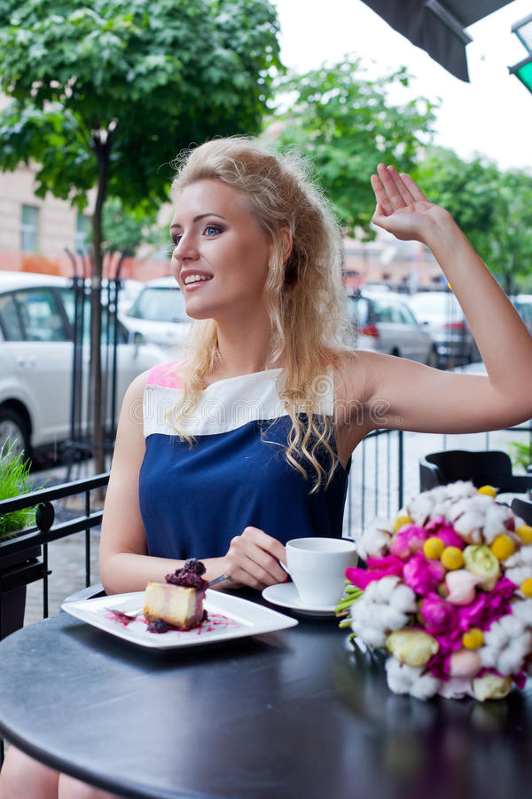 A beautiful young blond girl in summer dress at the table in pav