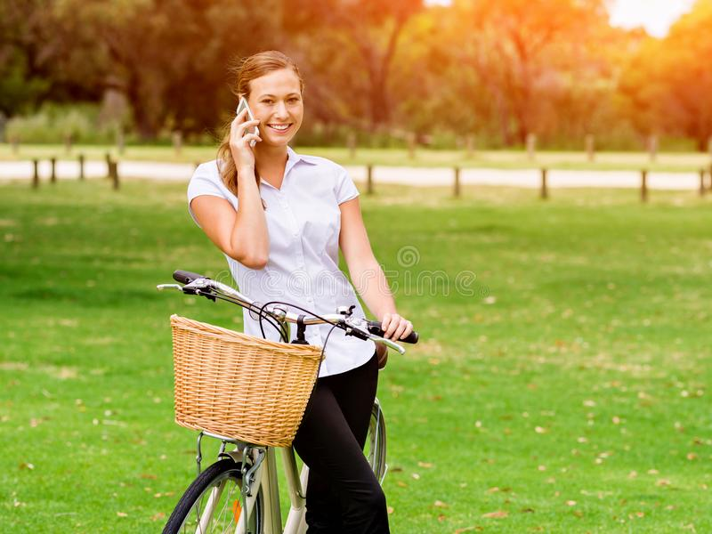 Beautiful young blond woman with bike in park talking over phone stock image