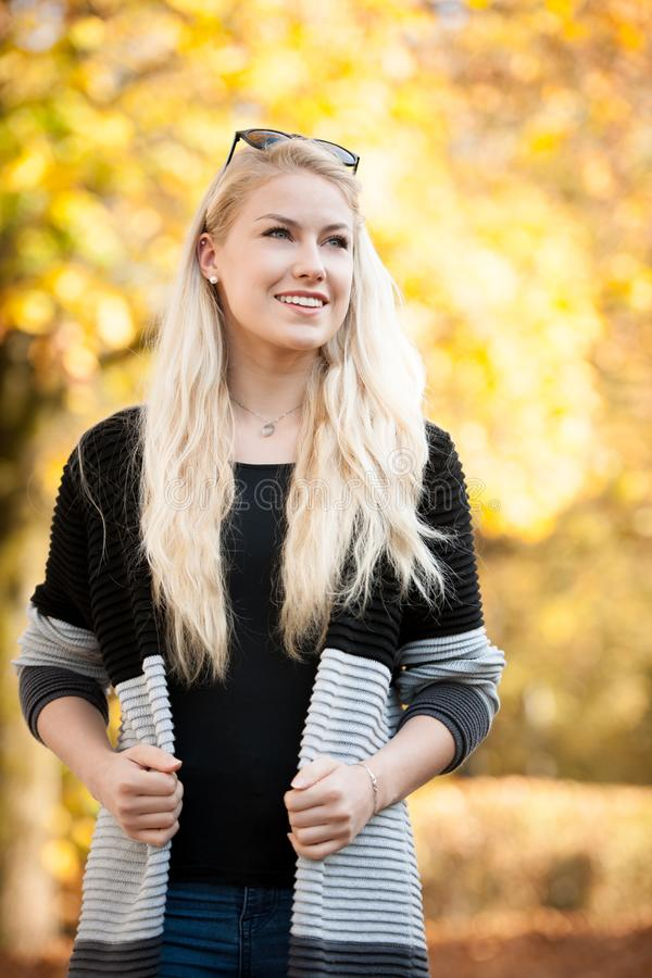 Beautiful young blond happy woman outdoor on early autumn afternoon stock photo