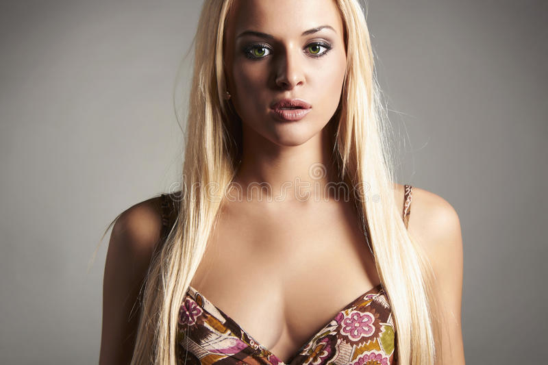 Beautiful young blond woman with big cleavage. Grey background. girl. Close-up portrait. green eyes stock photo