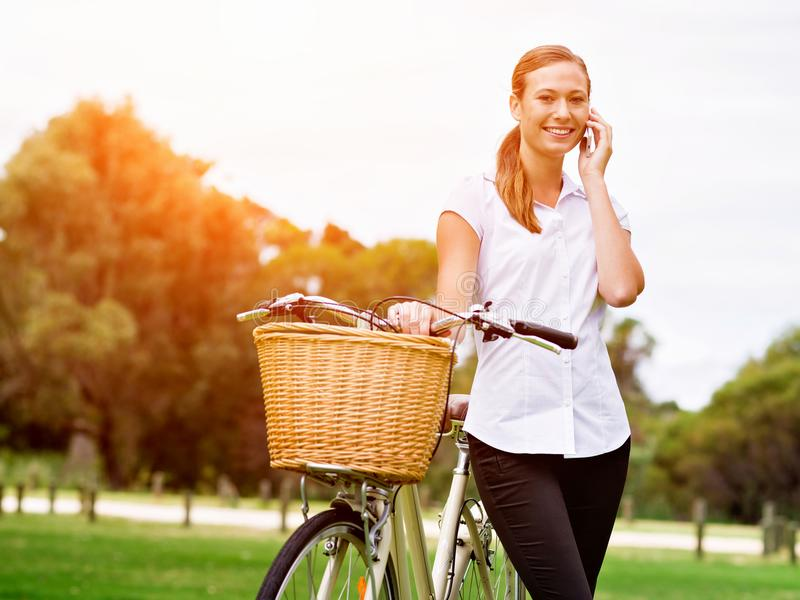 Beautiful young blond woman with bike in park talking over phone royalty free stock images