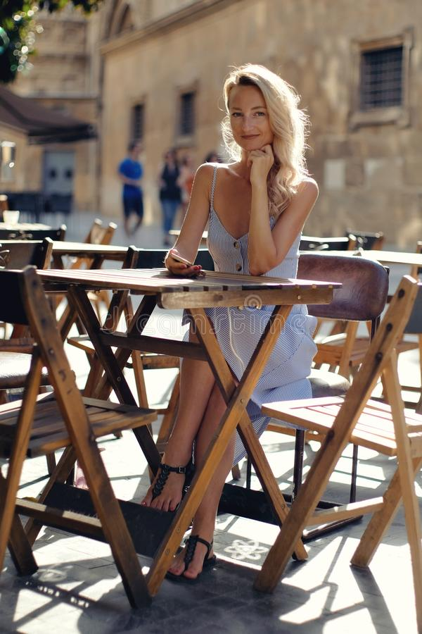 Beautiful young blond woman in blue summer dress sit at table at open air cafe outdoors restaurant smiling looking at camera royalty free stock photos
