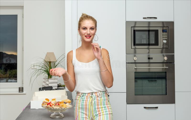Beautiful young blond woman eating cakes in the kitchen. A beautiful young blond woman eating cakes in the kitchen stock images