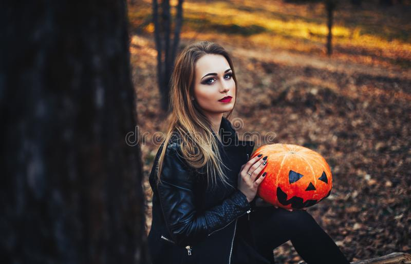 Beautiful young blond woman with extravagant make-up in a black leather jacket with wide open eyes and an open mouth with a. Pumpkin in hands stock images