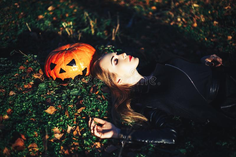 Beautiful young blond woman with extravagant make-up in a black leather jacket with wide open eyes and an open mouth with a. Pumpkin in hands royalty free stock photo