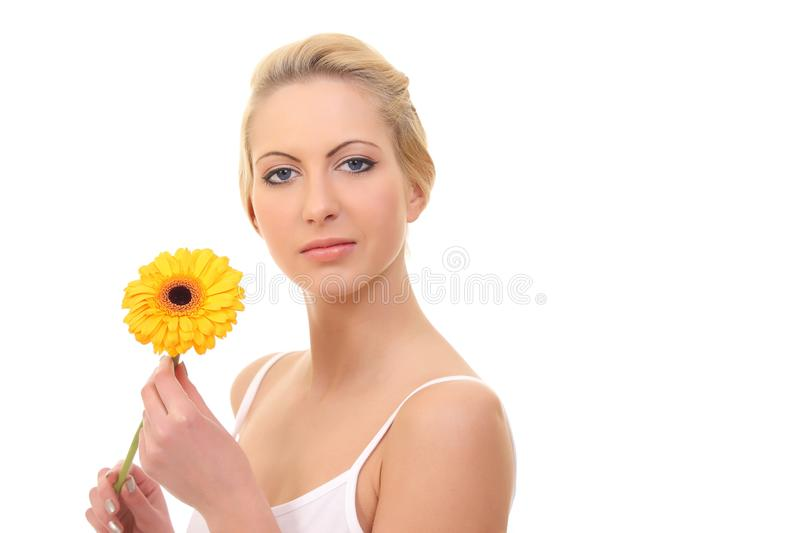 young blond woman with a flower in her hands royalty free stock image