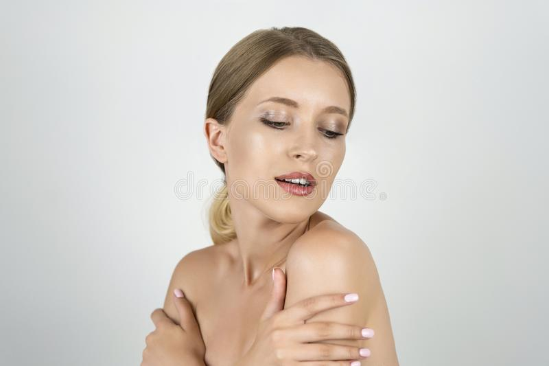 Beautiful young blond woman half a turn holding hands near shoulders isolated white background stock photo