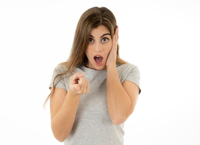 Happy young attractive woman shocked with a surprised funny face. Human expressions and emotions. Beautiful young blond woman with happy face pointing and making stock image