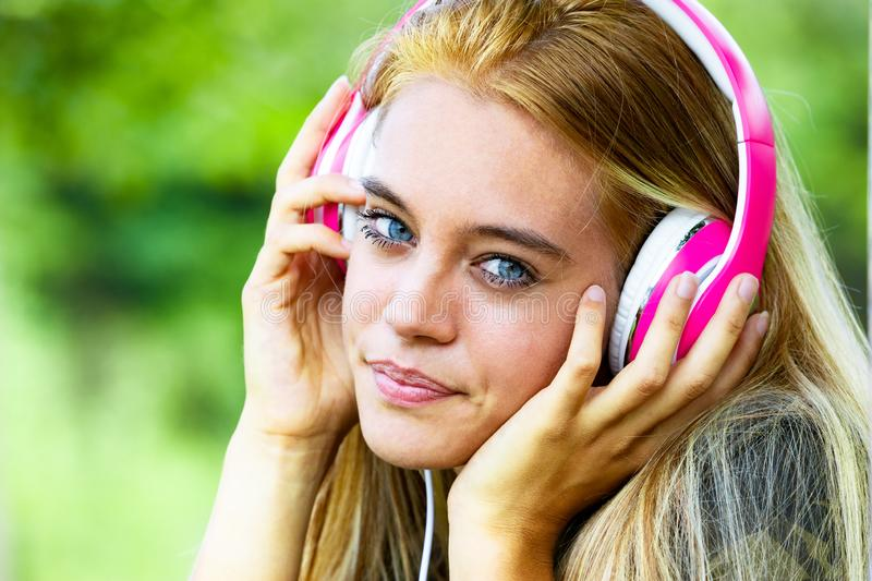 Beautiful young blond woman with headphones. Portrait of beautiful young blond woman with headphones listening to music, green nature background stock images