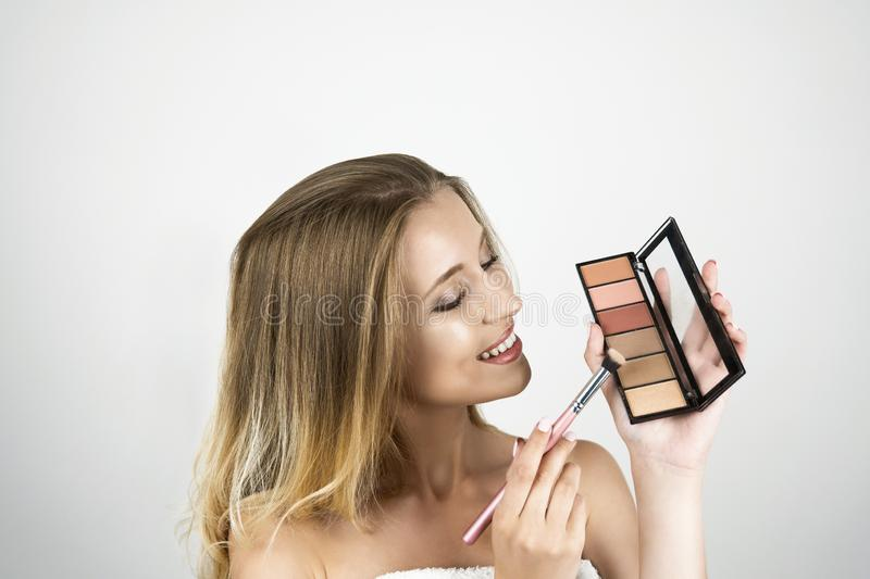 Beautiful young blond woman holding brush and eyeshagow palette isolated white background royalty free stock image