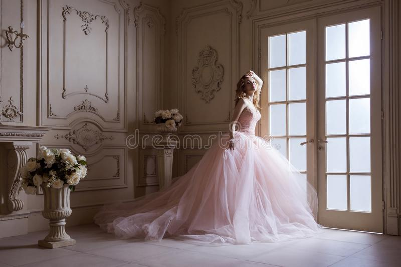 Beautiful young blond woman in luxurious long pink dress posing in vintage room interior royalty free stock photos