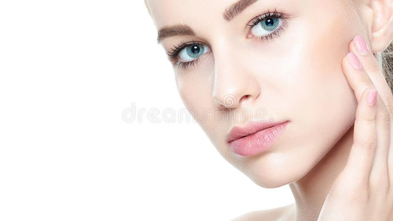 Beautiful Young Blond Woman with Perfect Skin touching her face. Facial treatment. Cosmetology, beauty and spa concept. Isolated on white background royalty free stock photos