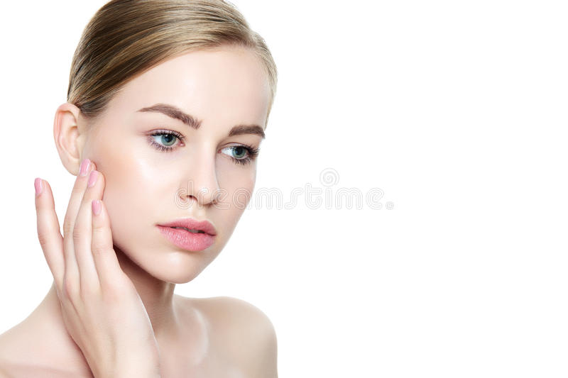 Beautiful Young Blond Woman with Perfect Skin touching her face. Facial treatment. Cosmetology, beauty and spa concept. Isolated on white background stock image