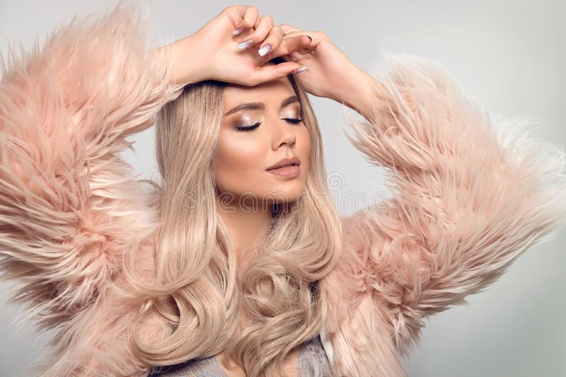 Beautiful young blond woman in pink fur caot. Winter fashion. Beauty Sexy Model Girl with long curly shiny hair and make-up royalty free stock photography