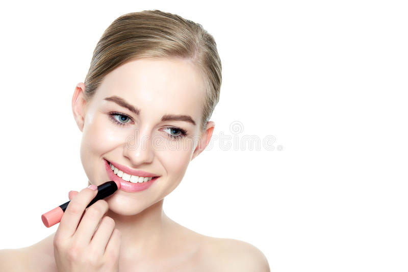 Beautiful young blond woman with full lips applying coral color lipstick stock images