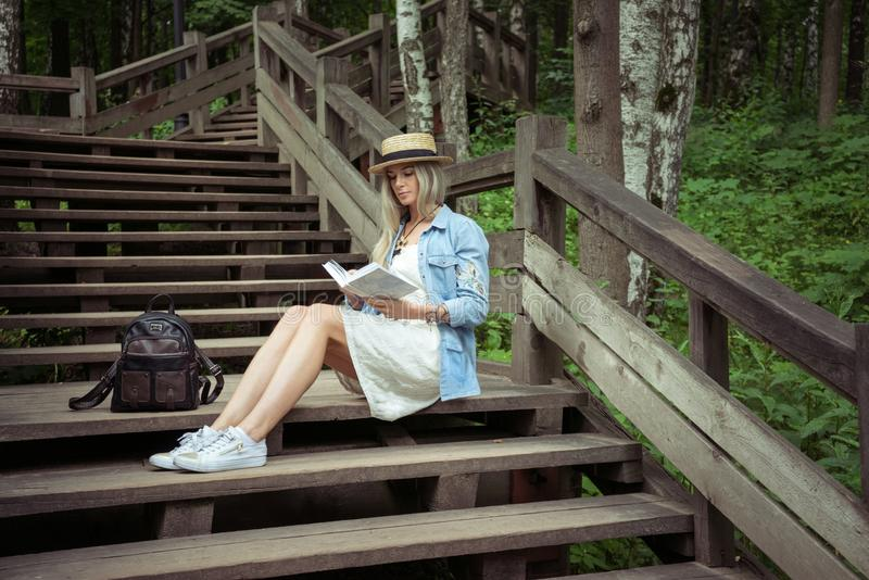 Beautiful young blond woman sitting on wooden stairs in the city park and reading a book. She has a white dress, a straw stock photos