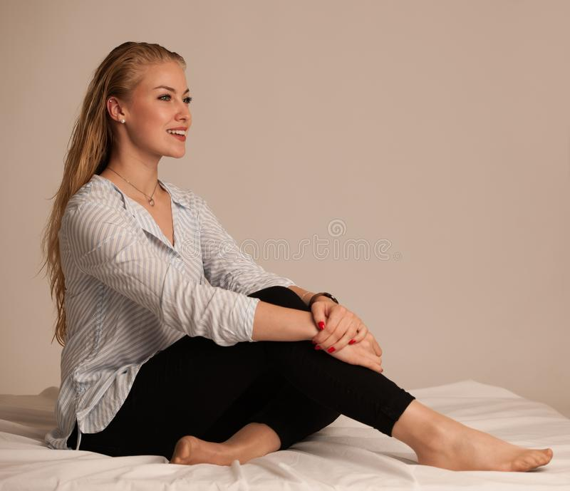 Beautiful young blond woman stting on bed royalty free stock photo