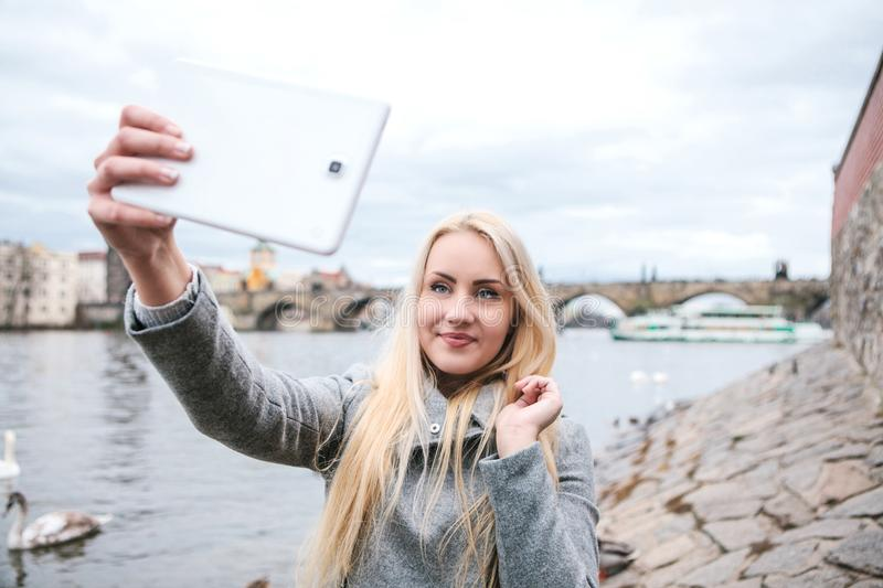 A beautiful young blond woman or tourist doing selfie. A beautiful young blond woman or tourist doing selfie or photographing herself in Prague in the Czech stock image