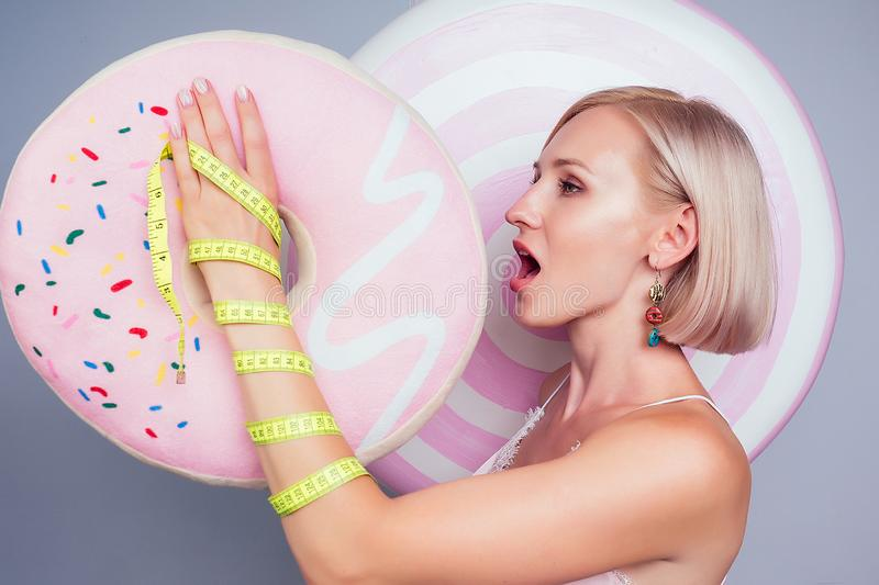 Beautiful young blonde Barbie sweet woman confectioner sexy model perfect makeup eat pink donut with measuring tape royalty free stock photo