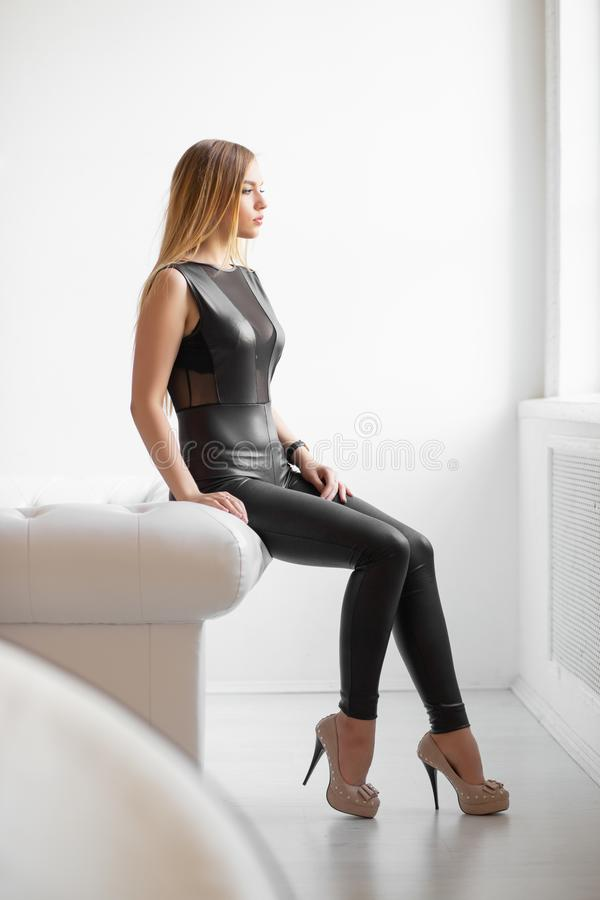 Beautiful young blonde. Posing in the studio dressed in a black leather suit royalty free stock photos