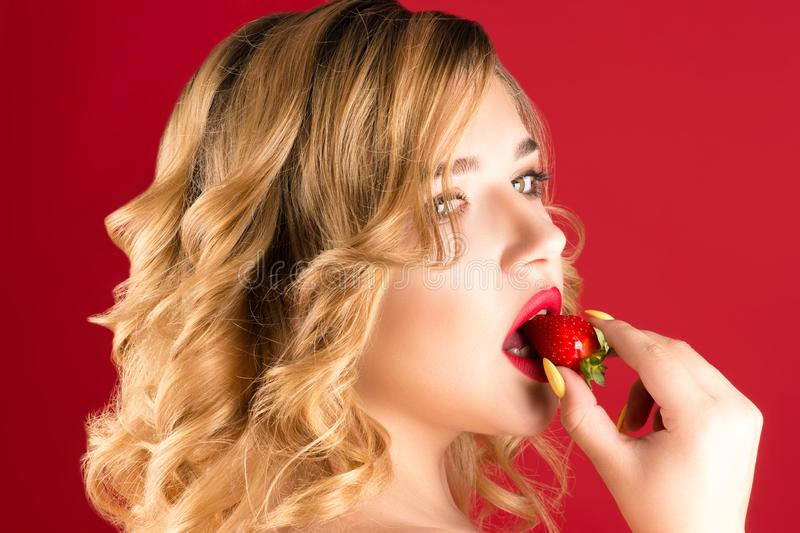 Beautiful young blonde eats strawberries with cream royalty free stock photo