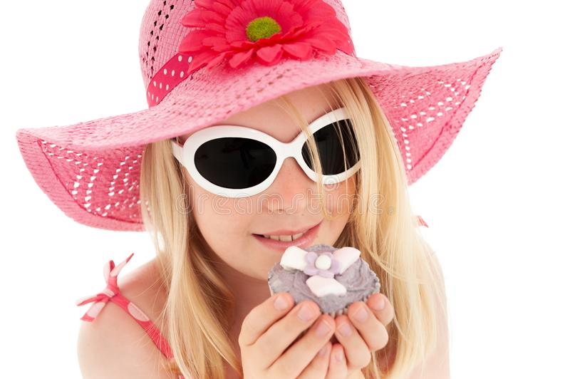 Beautiful young blonde girl in big pink floppy hat and white framed sunglasses holding a cup cake up to her face. White studio royalty free stock photography