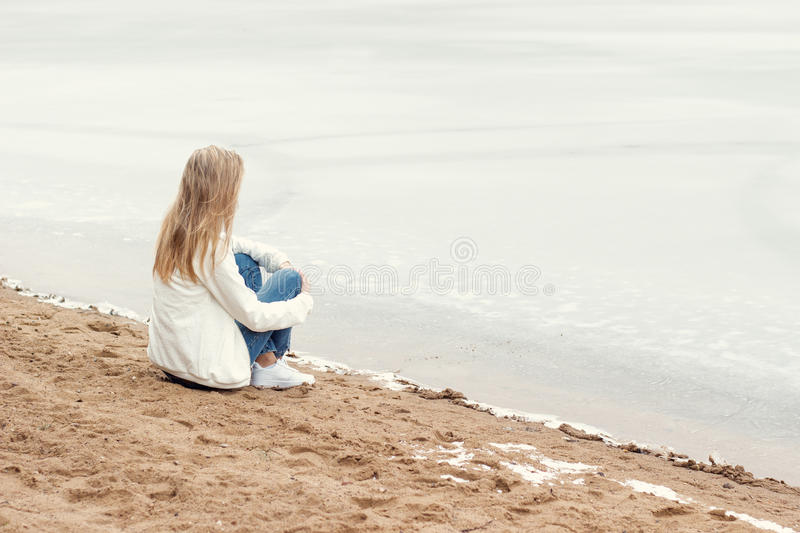 Beautiful young blonde girl in jeans and a white shirt sitting on the shore of the frozen cold of the lake near the forest in earl stock photos