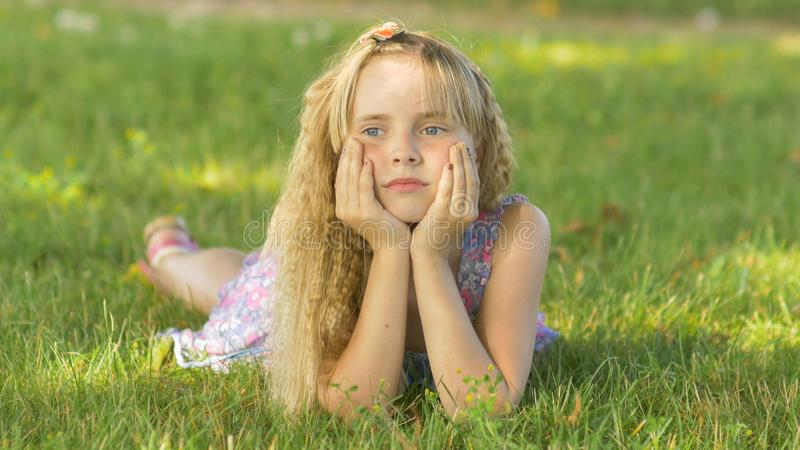 Beautiful young blonde girl lying on a field, green grass. Outdoors Enjoy Nature. Healthy Smiling Girl lying in Green stock image