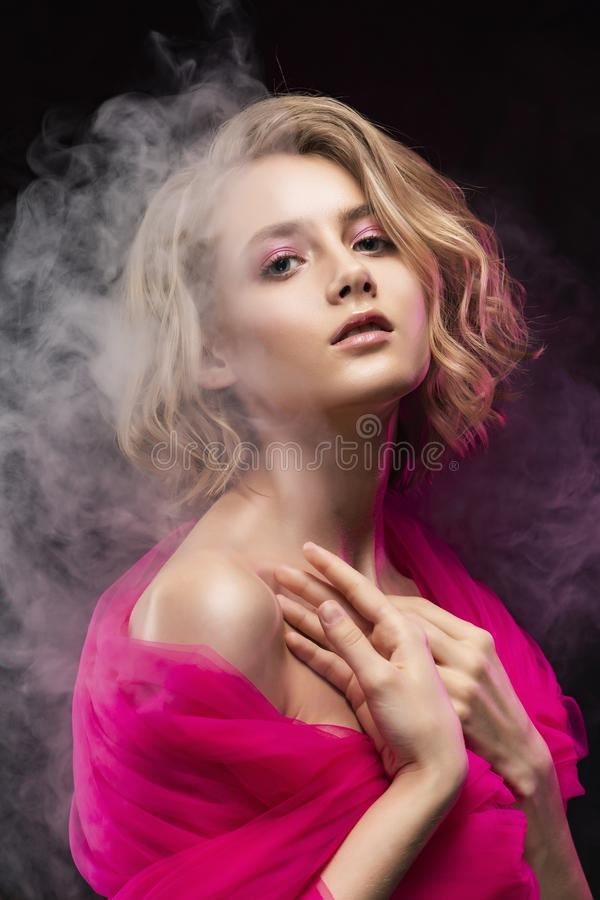 Beautiful young blonde girl with naked oily shoulders and curly hair, wrapped in a pink veil posing on a pink gradient background stock photos