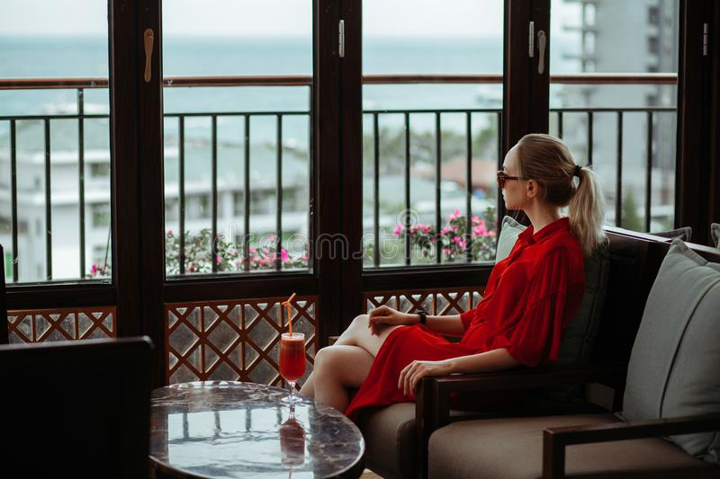 Beautiful young blonde girl in red dress and sunglasses drinking red cocktail from a glass on an open terrace of an stock image
