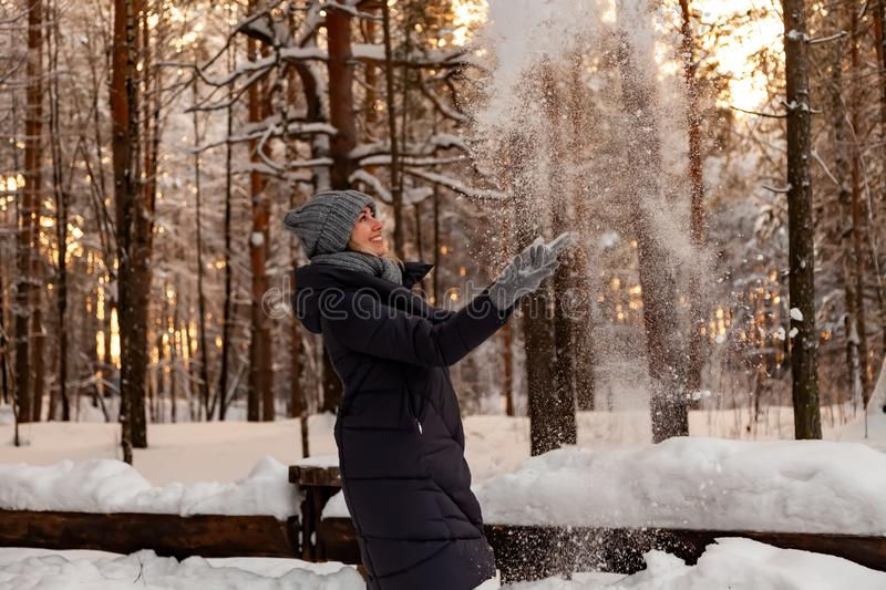 A beautiful young blonde girl in a winter coniferous forest is standing and catching with her hands the snow falling from the royalty free stock photography