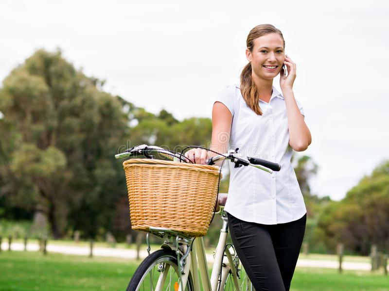 Beautiful young blonde woman with bike in park talking over phone stock images