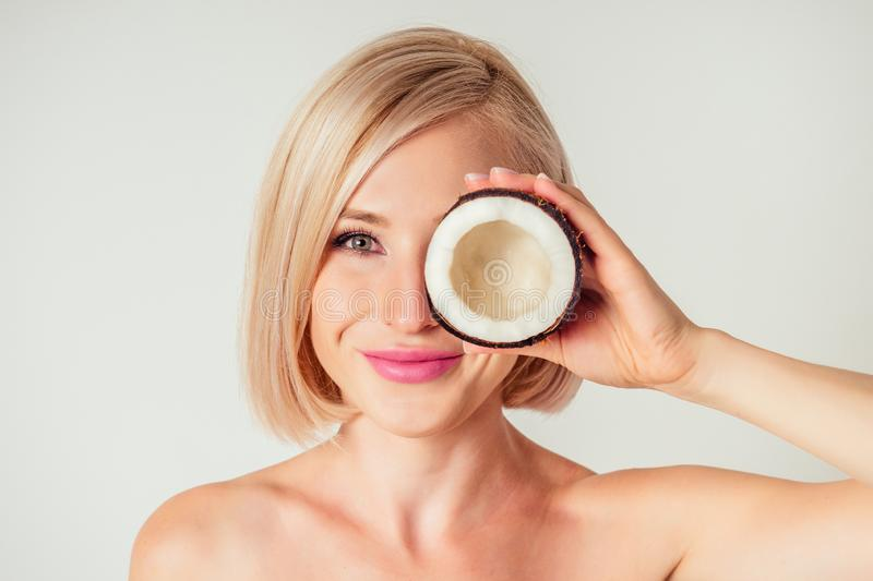 Beautiful young blonde hairstyle girl with a long eyelashes make-up and perfect skin with coconut in her hand in the stock photography