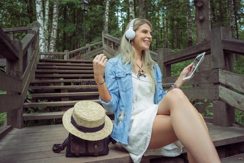 Beautiful young blonde hipster woman listening music in headphones in park with tablet in hands, sitting on wooden steps royalty free stock photo