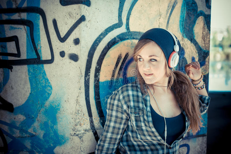 Beautiful young blonde hipster woman listening music stock photography